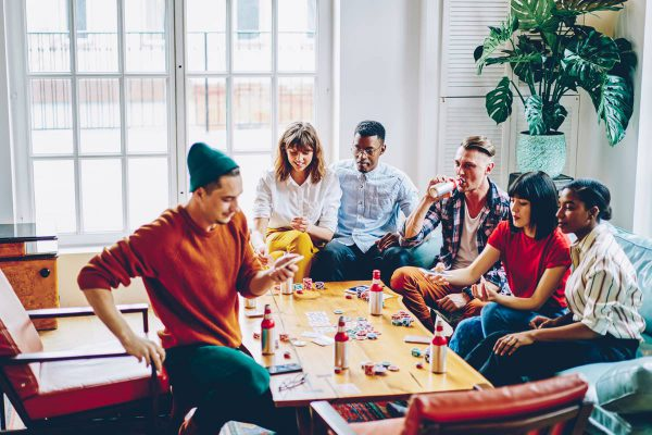 Diverse cheerful hipster guys drinking beverage and playing cards at table with chips for poker in modern apartment.Positive casual dressed multicultural friends spending free time together in flat