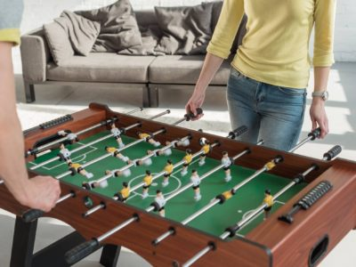 Couple playing foosball with one goalie