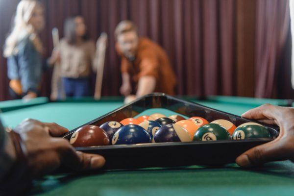 Hands setting up pool balls