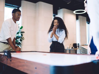 Cheerful African American woman amusing folding hands watching air hockey game with colleagues