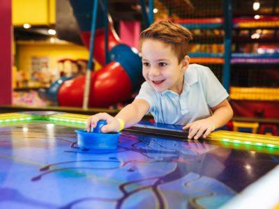 Joyful little boy playing air hockey