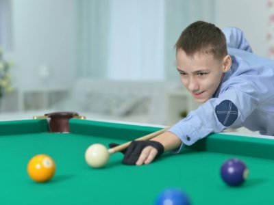 Boy shooting cue ball on pool table
