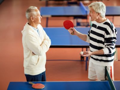 Annoyed ping pong trainer looking at mature player while explaining rules or details of game