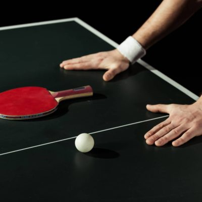 Hands on ping pong table with paddle and ball