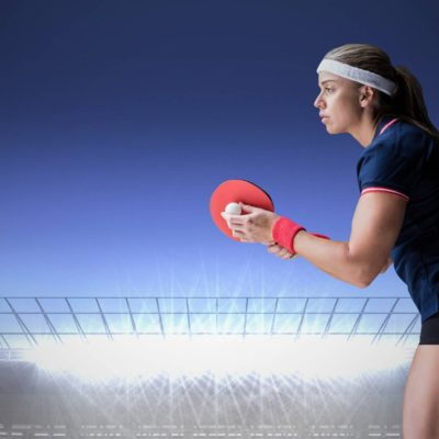 Digital composite of Table tennis player against stadium with bright lights and dark blue sky