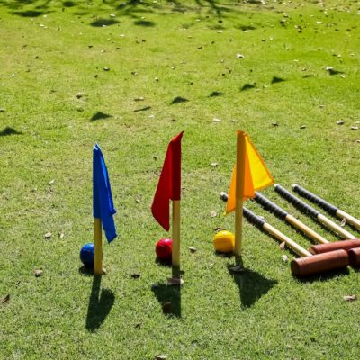 A high angle shot of balls and sticks used in Croquet on a grass-covered field