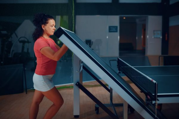 Woman folds ping pong table, tennis workout