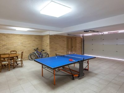 Ping pong table tennis table in the garage, with bicycles.