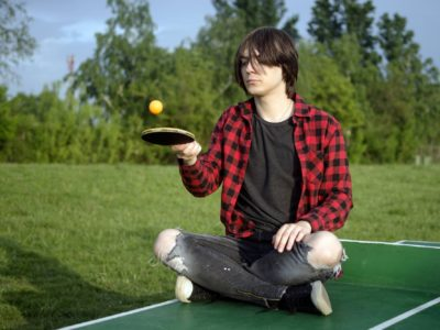 The teen boy is sitting on the green table for table tennis and playing alone with racket and ball outdoors.