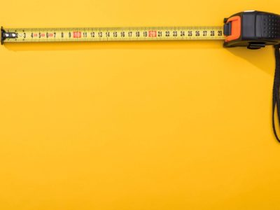 Tape measure on yellow background