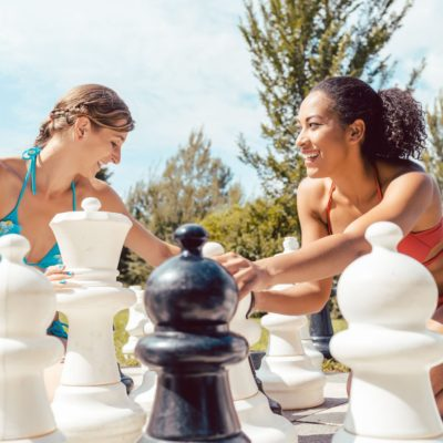 Two happy women playing big chess in yard