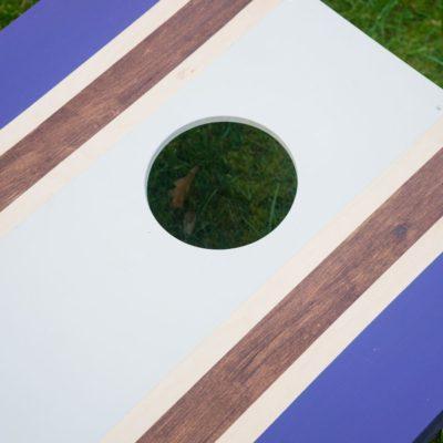 Purple and white cornhole board