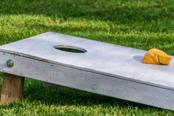 Gray cornhole board with yellow bag on top