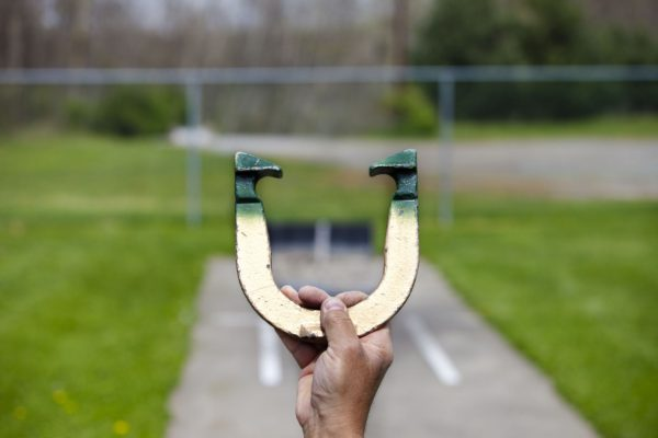 Player lines up to pitch a horseshoe in an outdoor court, hand and horseshoe in focus