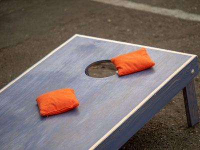 Orange beanbags sitting on blue cornhole board platform