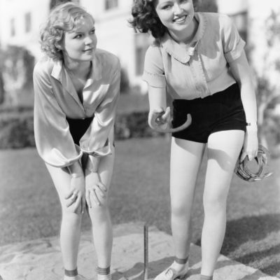 Two young women tossing horse shoes