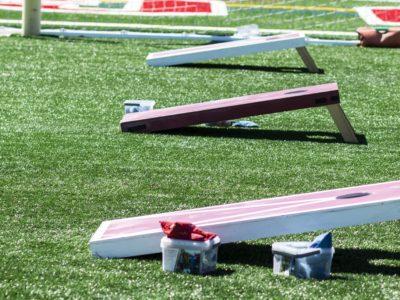 Three corn hole games set up on turf field